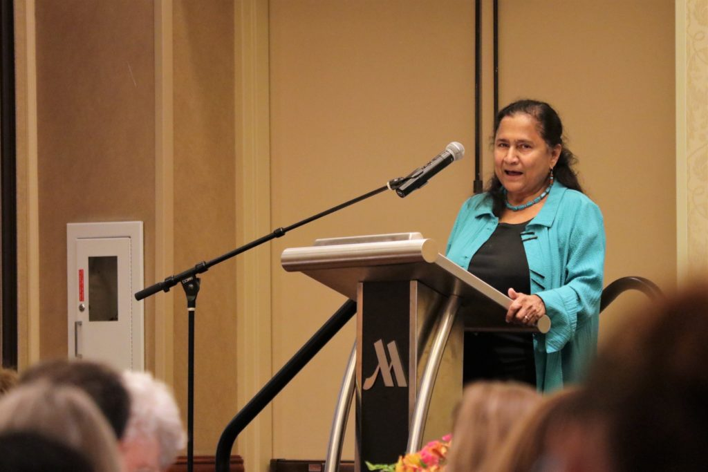An image taken from last years conference of a hispanic woman speaking in front of a large crowd in a conference hall