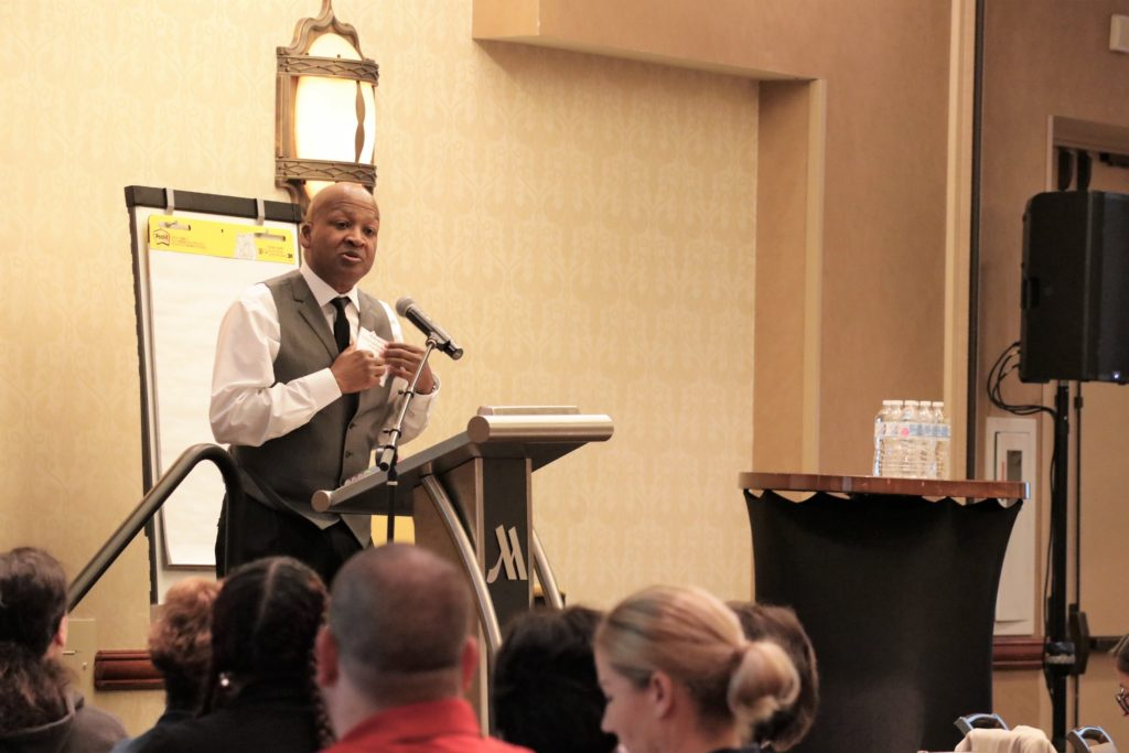 An image taken from last years conference of a black man speaking in front of a large crowd in a conference hall